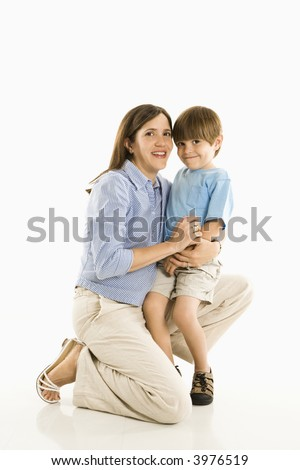 Mother kneeling down holding son against white background. - stock photo