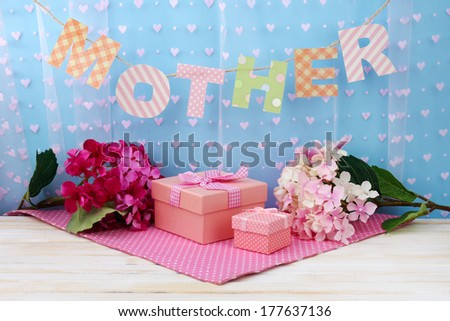 Mother- lettering of handmade paper letters on blue background - stock photo