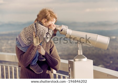 Mother lifting her young son up to look through a viewing binocular - stock photo