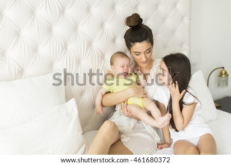 Mother, little girl and baby on the bed in the room