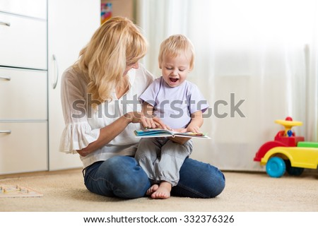 Mother looking at a book with her child son at home - stock photo