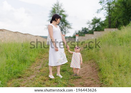 mother looking at daughter in sunglasses