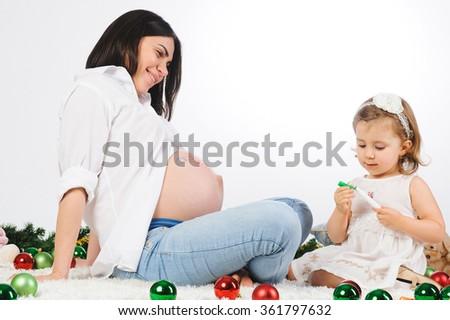 mother looking at girl closing green marker - stock photo