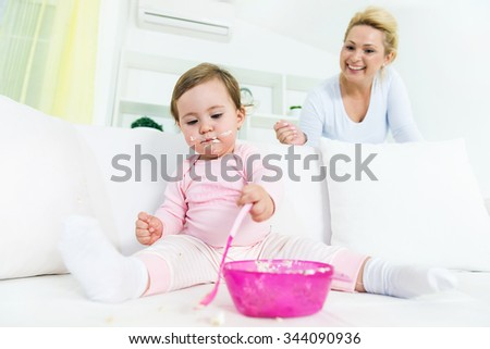 Mother looking her little baby girl while she eating her first cake alone.Funny face baby.Shallow doff, wide angle - stock photo