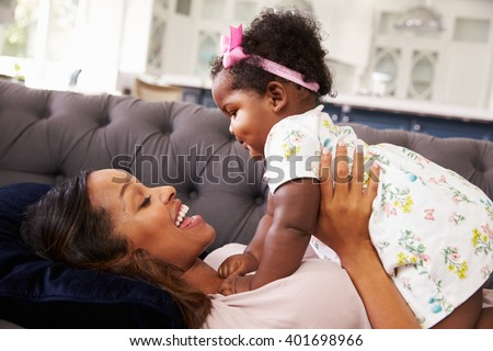 Mother lying back holding her toddler daughter on top of her - stock photo