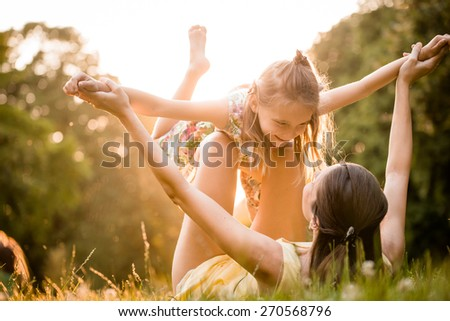 Mother lying down on grass and plays with her daughter on airplane - stock photo