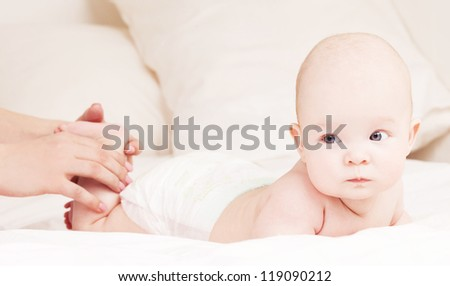 Mother massaging baby in bed at home - stock photo