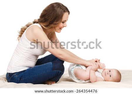 Mother massaging baby on white background. young mum and the kid on a white. doctor massaging or doing gymnastics baby - stock photo