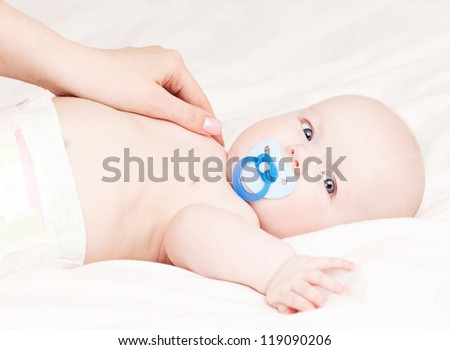 Mother massaging her four month old baby in bed at home - stock photo