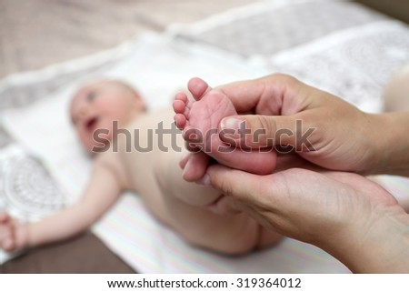 Mother massaging the newborn baby boy foot at home
