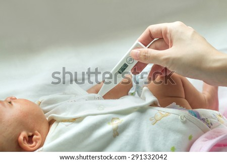 mother measures the temperature of a smiling child