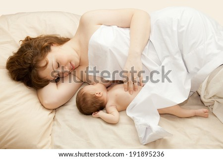 Mother nursing (breast feeding) her newborn baby while laying in the bed. - stock photo