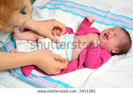 mother of a newborn baby girl changing diaper, while baby is not very happy!! - stock photo