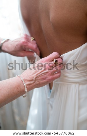 Mother of the bride zipping up and buttoning brides dress.