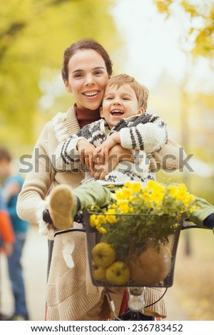 Mother on a bicycle having fun with her cute little son sitting on the handlebars - stock photo