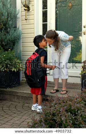 Mother on her front steps kissing her young elementary son good-bye as he heads off for school. - stock photo