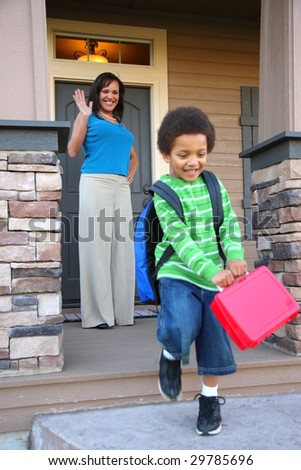 Mother on porch waves to child heading off to school