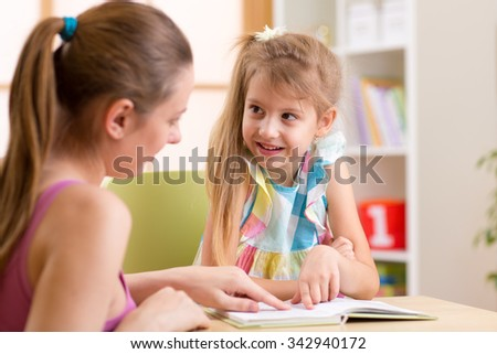Mother or teacher woman helping child girl with homework - stock photo