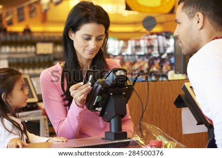 Mother Paying For Family Shopping At Checkout With Card - stock photo