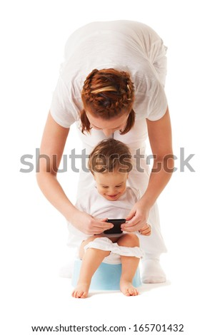 Mother performs potty training with her son using smartphone - stock photo