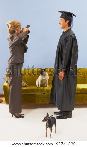 Mother photographing graduate son - stock photo