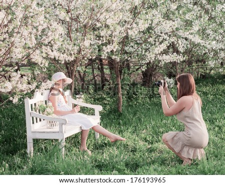 Mother photographing her daughter at spring garden