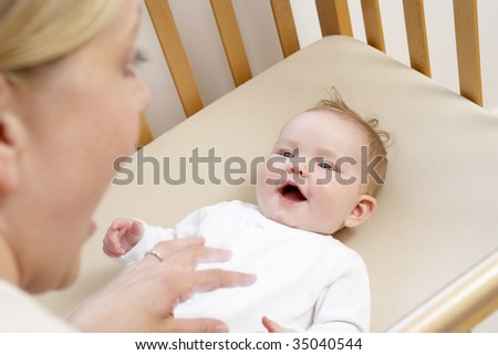 Mother Playing With Baby In Cot