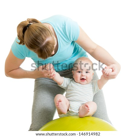 mother playing with baby on gymnastic ball - stock photo