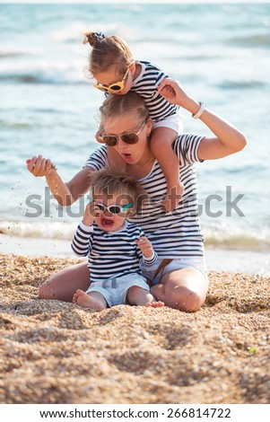 Mother playing with children on the beach - stock photo