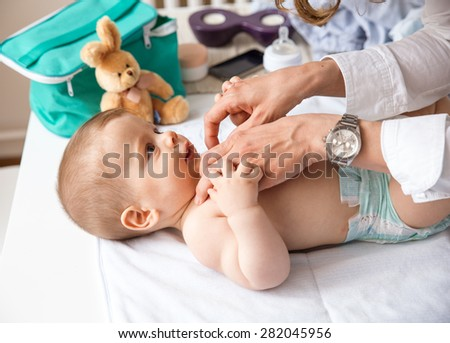 Mother playing with her baby  at home. - stock photo