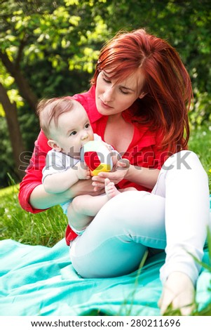mother playing with her baby boy in park - stock photo