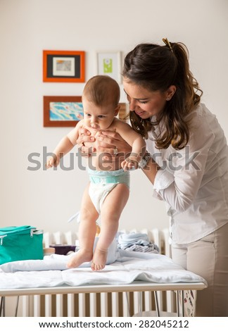 Mother playing with her baby on the bed at home. - stock photo