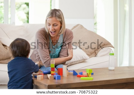 Mother playing with her child at home - stock photo