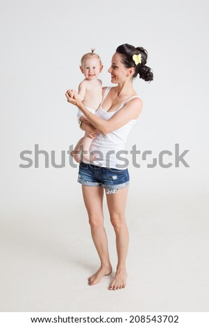 Mother playing with her daughter holding her in his arms. - stock photo