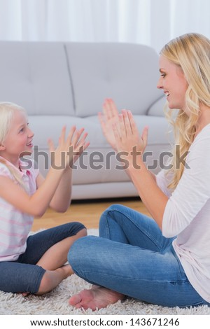Mother playing with her daughter in the living room - stock photo