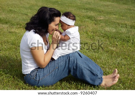 Mother playing with her daughter on the grass - stock photo