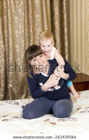 Mother playing with her son at bedtime on the bed in the bedroom - stock photo