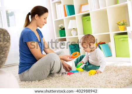 Mother playing with her son on floor with toys - stock photo
