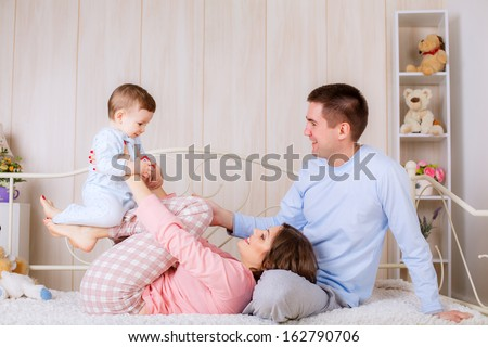 mother playing with her son on the bed