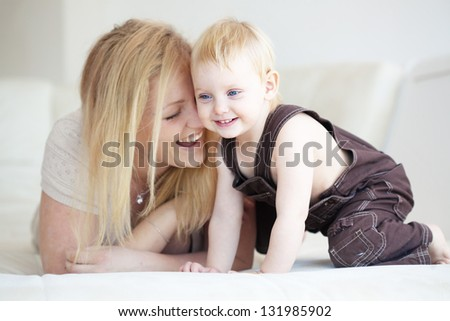 Mother playing with her toddler child at home - stock photo