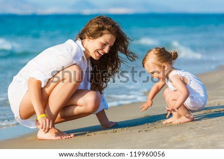 Mother playing with little daughter on the beach - stock photo