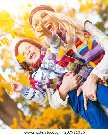Mother playing with son in autumn park - stock photo