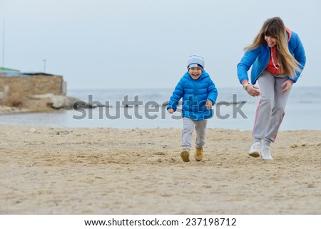 mother playing with son on the beach in soft selective focus - stock photo