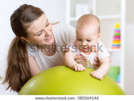 mother plays with baby on fit ball  - stock photo