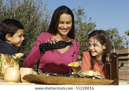 mother pouring olive oil on bread