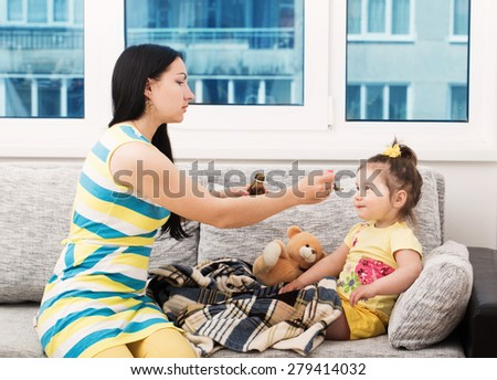 Mother pouring tasty syrup to ease her little girl's cough - stock photo