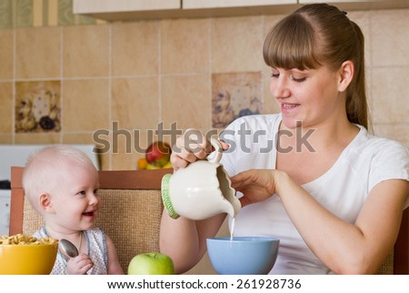 Mother preparing breakfast with milk for her daughter - stock photo