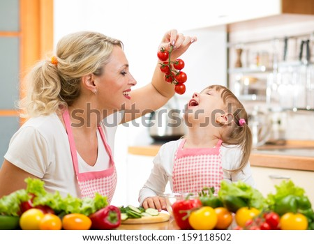 mother preparing dinner and feeding kid  tomatoes in kitchen - stock photo