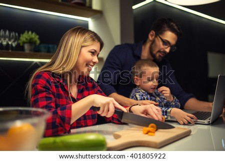 Mother preparing food while dad and son using laptop. Selective focus. - stock photo