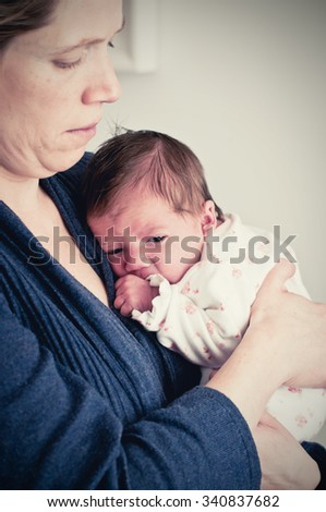 Mother protecting her new born baby girl - stock photo